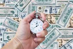 Cronometro sopra la priorità bassa dei soldi Fotografia Stock