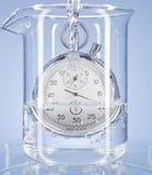 Cronometro in un vetro con acqua Fotografie Stock