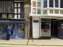 Crooked architecture on historic buildings. The wonky walls and doors of shops along the main street of Dartmouth in Devon, England Royalty Free Stock Photography