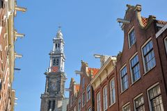 Crooked and colorful heritage buildings, located along Bloemstraat street, with Westerkerk church clocktower in the background royalty free stock image