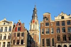 Crooked and colorful heritage buildings, located along Kloveniersburgwal Canal, with Zuiderkerk church clocktower in background stock photography