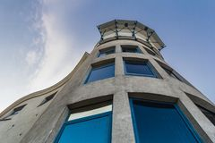 A crooked concrete building with blue windows. stock photography