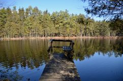Crooked Dock. A crooked old wooden dock on a still reflective lake on a sunny day. The scene is common in the Pine Barrens of Southern New Jersey Stock Photography