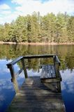 Crooked Dock. A crooked old wooden dock on a still reflective lake on a sunny day with white clouds in the sky. The scene is common in the Pine Barrens of Royalty Free Stock Photography