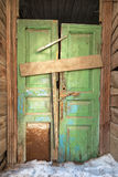 Crooked green door in old wooden house. Royalty Free Stock Photography