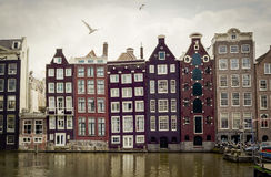 Crooked houses on a canal with seagulls in Amsterdam,Holland Stock Photo