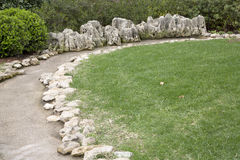 Crooked path and flowing water around  lawn Royalty Free Stock Photos