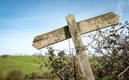 English countryside public footpath sign. A crooked public footpath sign covered in moss and lichen directing hikers on their route through the English Royalty Free Stock Photography