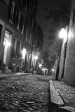 Crooked streets of boston. Black and white image of an old 19th Century cobble stone road in Boston Massachusetts, lit only by the gas lamps revealing the Stock Photography
