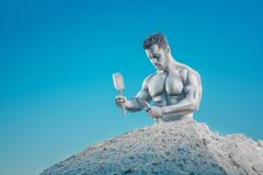 Crop of Atlas with hammer and chisel hollowing rock. Crop of Atlas with hammer and chisel hollowing rock around himself. Portrait of young handsome silver stock image