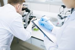 Scientists writing results of research under microscope. Crop back view of female microbiologist writing down into clipboard data received from men analyzing Stock Images