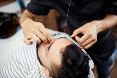 Crop barber threading eyebrows of client Stock Photo