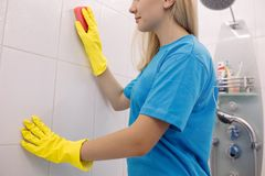 Crop of blonde woman from cleaning company cleaning wall in white bathroom. stock photos