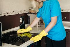 Crop of blonde woman in protective gloves with rag cleaning electric stove. royalty free stock photography