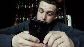 Man concentrating on using smartphone. Crop close-up view of mobile phone held in hands of brunette male in dark clothes sitting at bar counter with hanging stock video footage