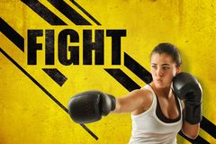 Crop close-up of young woman in boxing gloves holding one hand out, against yellow wall with `FIGHT` title and black stock photos