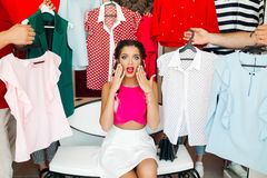 Frustreted brunette in pink having a problem of choosing clothes. Crop, closeup portrait of young girl in pink blouse waching on camera and holding hands stock photos