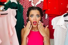 Frustreted brunette in pink having a problem of choosing clothes. Crop, closeup portrait of young girl in pink blouse waching on camera and holding hands royalty free stock photography