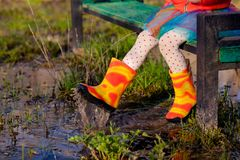Crop colorful girl in gumboots on bench Stock Photography