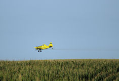 Crop Duster Airplane. Crop duster spraying cornfield stock photo