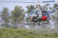 Crop Duster and Crew. Crew members work together preparing and refilling a helicopter specially equipped to chemical spray a berry crop in Sumas, Washington on royalty free stock photography