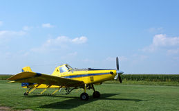 Crop duster on ground. Yellow crop duster parked near a corn field royalty free stock photo