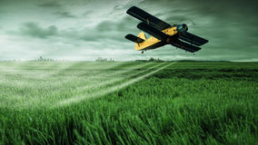 A crop dusting plane working over a field Royalty Free Stock Images