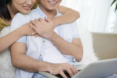 Crop embracing couple watching laptop royalty free stock photography