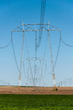 Crop field electric power towers Royalty Free Stock Images