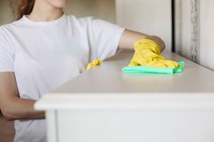 Crop of girl wearing in yellow protective rubber gloves, wiping furniture. royalty free stock image