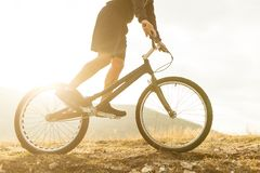 Crop guy riding bicycle in countryside. Anonymous man in sportswear riding modern sport bicycle on rough ground in majestic nature stock photos