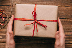 Crop hands holding wrapped present on table Stock Photos