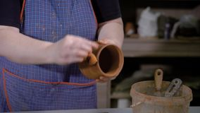 Crop hands of talented potter wearing apron,holding beautiful earthenware in hands and standing in craft studio. Master making jug of clay stock footage