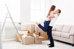 Happy couple hugging near unpacked boxes Royalty Free Stock Images