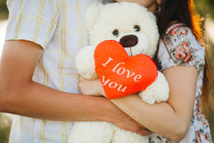 Crop of happy couple standing and embracing with teddy bear with red heart with words `I love you`. Side view of husband looking o Stock Photography