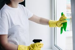 Crop of housewife cleaning dirty window. Concept of housework and apartment service. Crop of incognito brunette housewife cleaning dirty window. Housemaid stock image