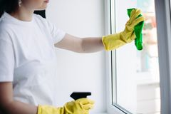 Crop of housewife cleaning dirty window. Concept of housework and apartment service. royalty free stock image