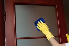 Crop of housewife hands wearing yellow gloves, cleaning dirty window. royalty free stock images