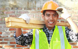 Crop images of man worker carrying wood smiling Stock Photo
