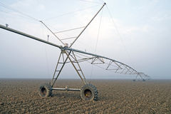 Crop Irrigation using the center pivot sprinkler system in the winter fog . Stock Image