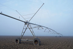 Crop Irrigation using the center pivot sprinkler system in the winter fog . Royalty Free Stock Photo