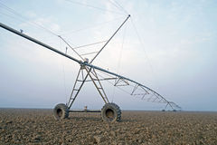 Crop Irrigation using the center pivot sprinkler system in the winter fog . Stock Photo