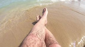 Crop of male legs on beach stock video