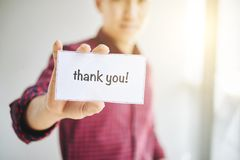 Crop man holding card with Thank You words. Crop male wearing checkered shirt holding card with inscription thank you in hands royalty free stock photography