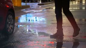Crop of man stepping in puddle on street. Crop shot of car splashing water over man`s feet in puddle on pavement reflecting night city lights. Unrecognizable stock video footage