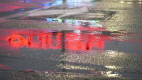 Crop of man stepping in puddle on street. Crop shot of man splashing water in puddle on pavement reflecting night city lights. Unrecognizable person running stock footage