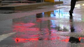 Crop of man stepping in puddle on street. Crop shot of man splashing water in puddle on pavement reflecting night city lights. Unrecognizable person running away stock video