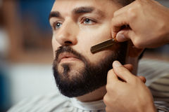 Crop man trimming beard of client. Anonymous barber shaving slightly beard of young man using sharp razor Stock Photography