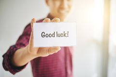 Crop man wishing Good Luck. Crop male wearing checkered shirt holding card with Good Luck words in hands Stock Photos