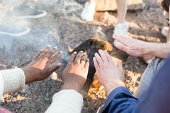 People warming hands over fire. Crop multiracial people warming hands near fire during nice beach party stock image